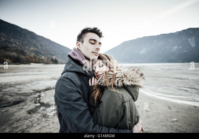 Young loving couple hugging, lake and mountains on background, love and romance concept - Stock Image
