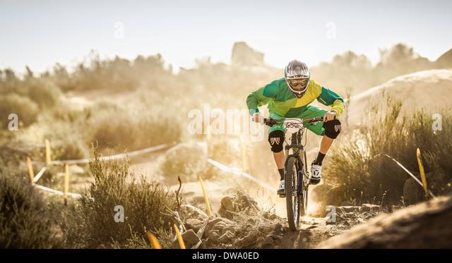 Male mountain biker racing on dusty dirt track, Fontana, California, USA - Stock Image
