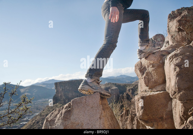 woman climbs rocks - Stock Image