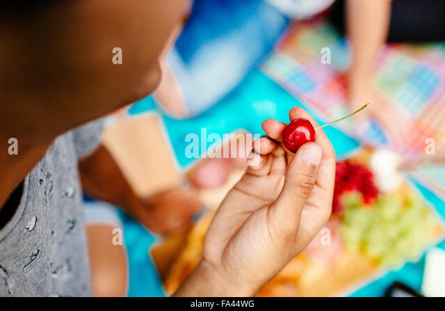 Cropped image of man holding cherry at park - Stock-Bilder