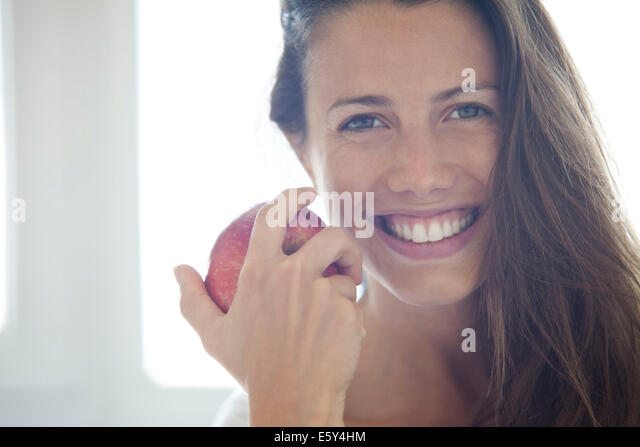 Woman holding apple, portrait - Stock Image