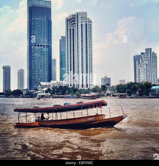 Thailand, Bangkok, River boat and cityscape - Stock Image