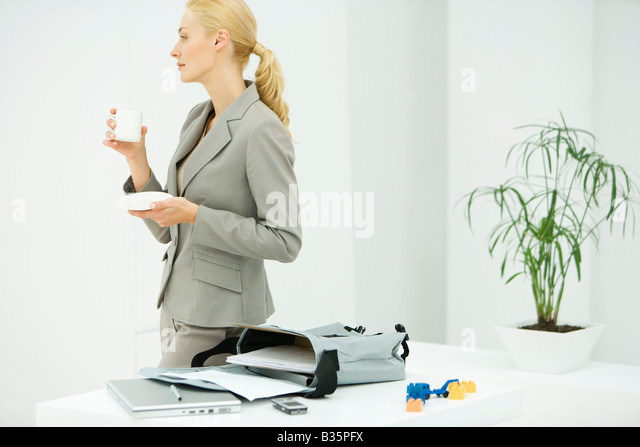 Professional woman holding coffee cup, looking away, bag with laptop and documents on table - Stock-Bilder