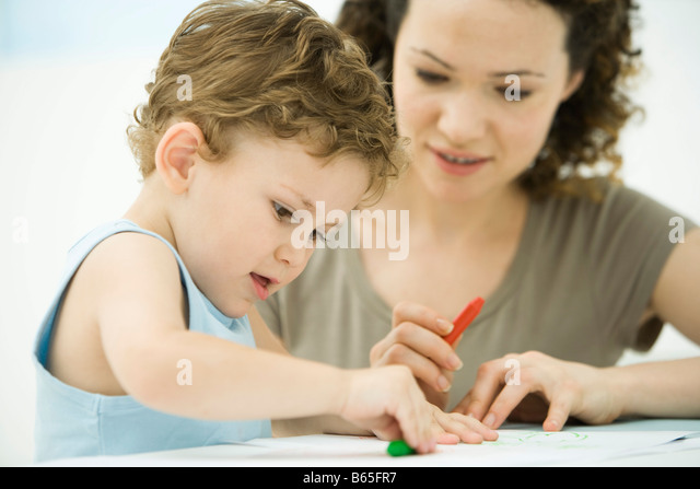 Mother and son sitting together, coloring with crayons - Stock-Bilder