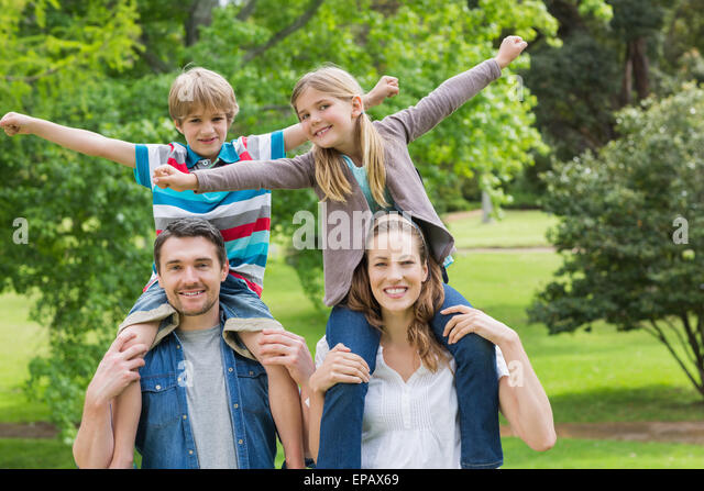 Happy parents carrying kids on shoulders at park - Stock Image