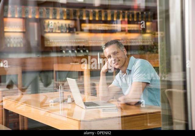Businessman using laptop, view through window - Stock-Bilder