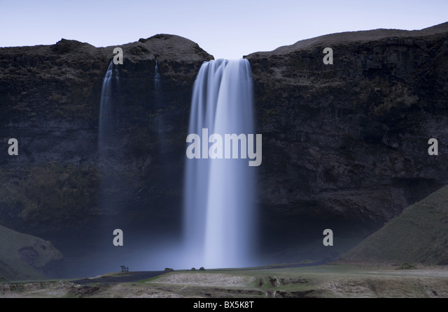 Seljalandsfoss Waterfall captured at dusk using long exposure to record movement in water, near Hella, southern - Stock Image