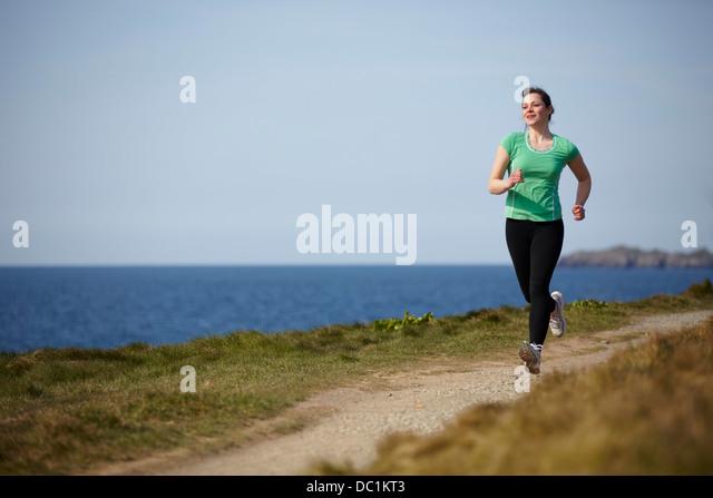 Young woman running along coastal path - Stock-Bilder