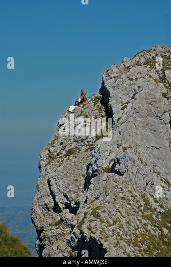 Switzerland man on mountain having lunch alone on steeo slope - Stock Image