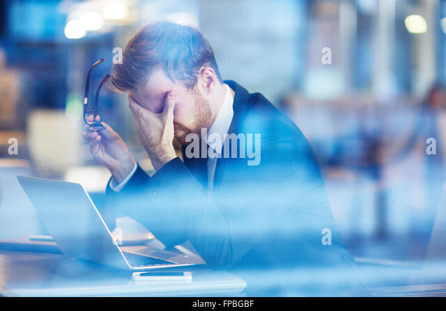 Depressed businessman sitting with laptop - Stock Image