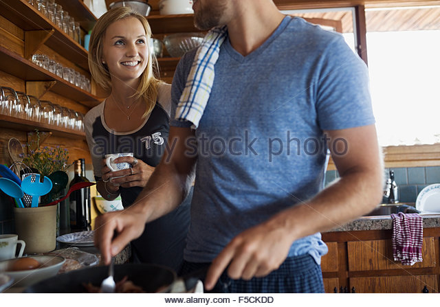 Young couple cooking breakfast in cabin kitchen - Stock Image