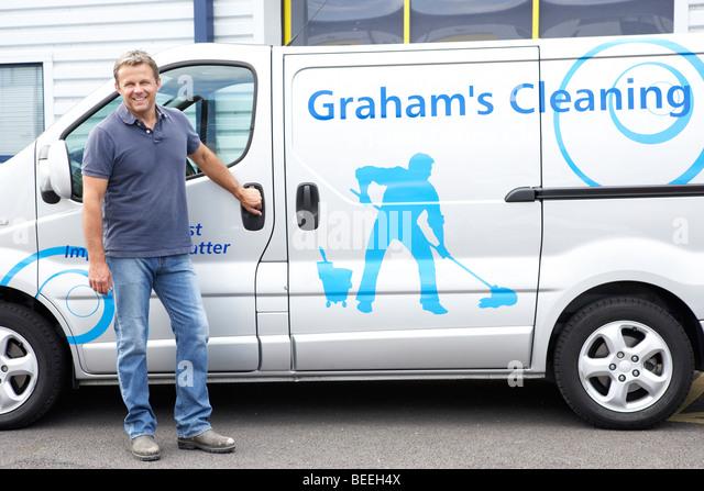 Cleaner standing next to van - Stock Image