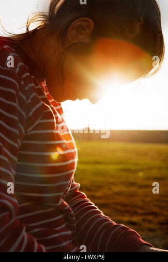 South Africa, Back lit mid adult woman looking down - Stock Image