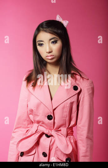 Stylish Japanese Girl in Pink Outwear over Colored Background - Stock Image
