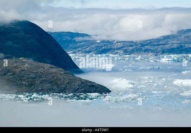 Mountains and mist above Sermilik Fjord, East Greenland - Stock Image