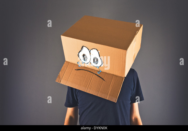 Man with cardboard box on his head and sad crying face expression. Concept of sadness and depression. - Stock Image