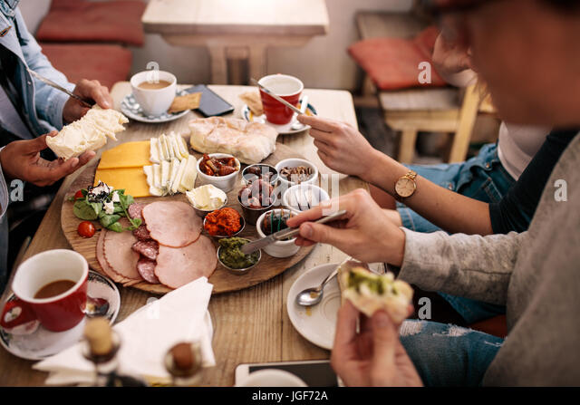 Close up of young people sitting around cafe table and eating with focus on hands and food. Group of students having - Stock Image