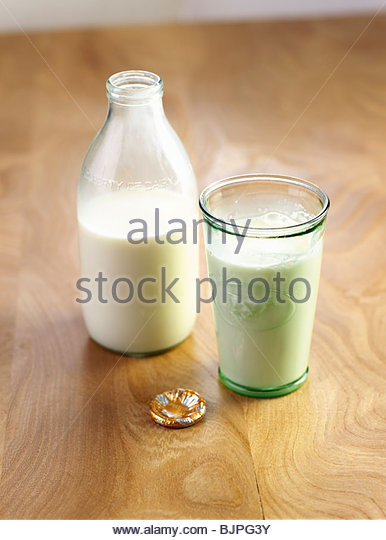 Milk bottle and a glass of milk - Stock Image