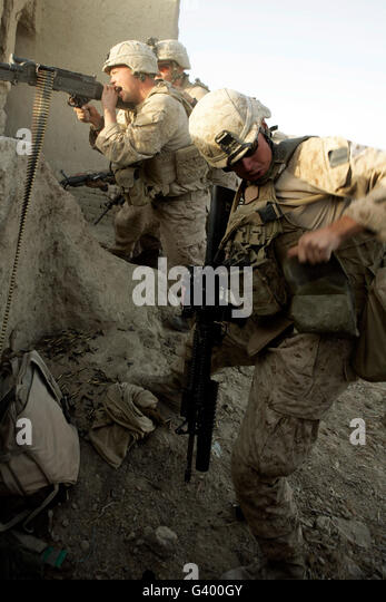 A U.S. Marine reaches for more rounds during combat. - Stock Image