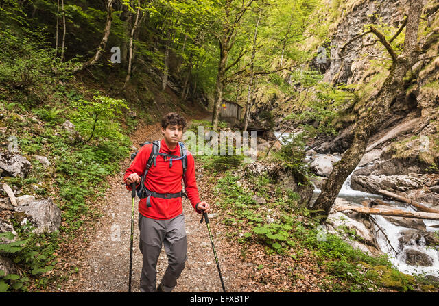 Young man hiking on river path, Oberstdorf, Bavaria, Germany - Stock-Bilder