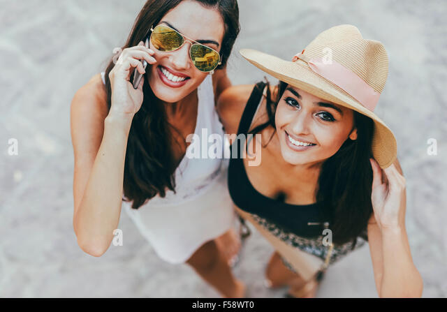 Portrait of two beautiful girls in summer clothes smiling and talking on phone - Stock Image
