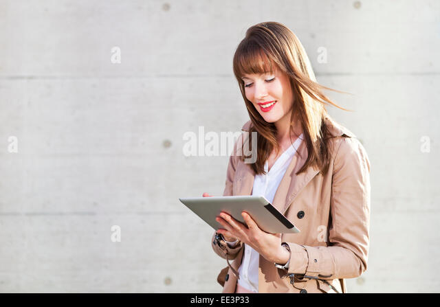 Young woman using digital tablet outdoors, Munich, Bavaria, Germany - Stock-Bilder