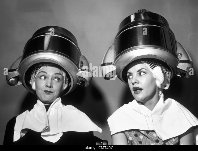 1950s TWO WOMEN SITTING TOGETHER GOSSIPING UNDER HAIRDRESSER HAIR DRYER - Stock Image