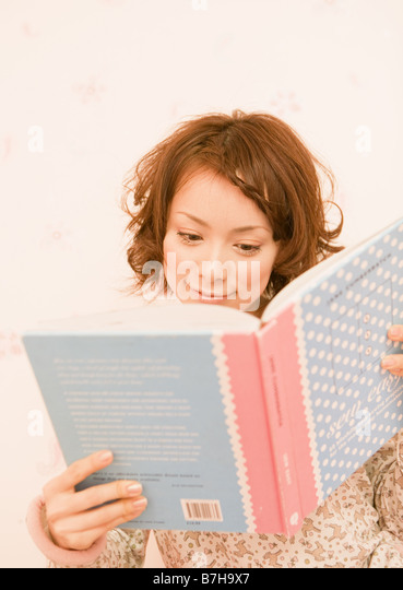 A woman reading a book - Stock Image