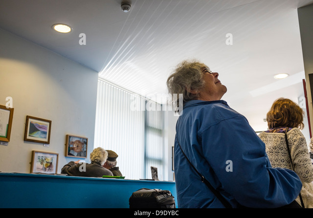 People looking at the art on show at the opening of an exhibition of amateur paintings, Wales UK - Stock-Bilder