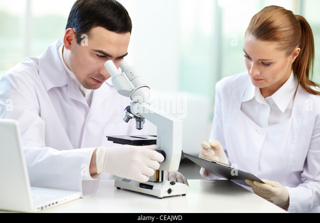 Serious clinicians studying chemical elements in laboratory - Stock Image