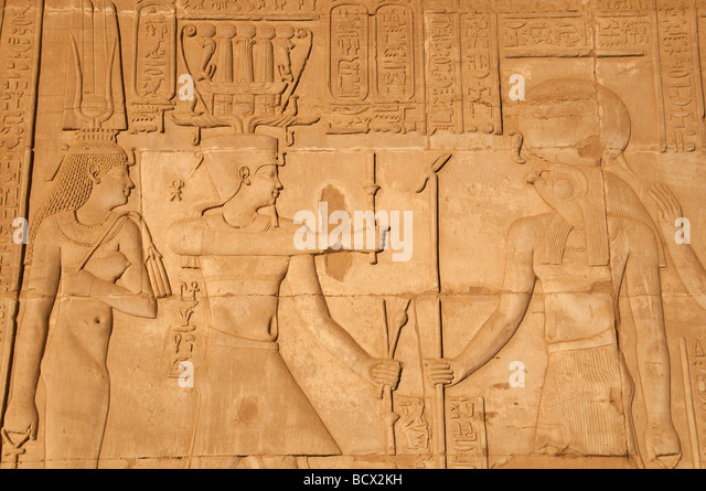 Egypt Kom Ombo temple wall reliefs pharaoh queen honor falcon-headed god Horus weating solar disc - Stock Image