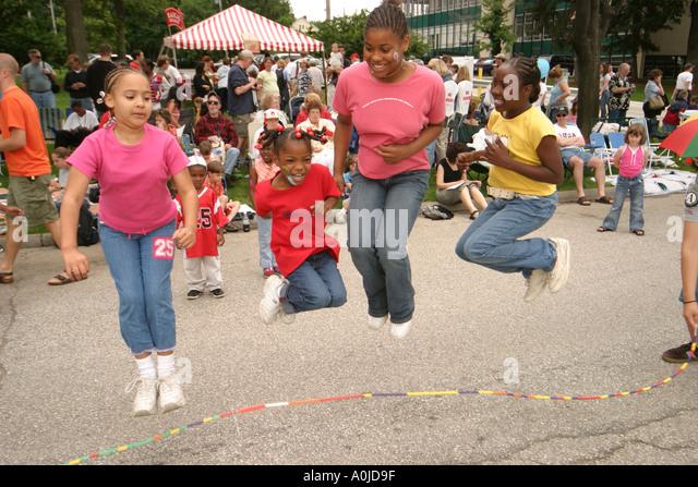 Cleveland Ohio University Circle Parade the Circle Arts Cultural Festival Black girls jump rope happy - Stock Image
