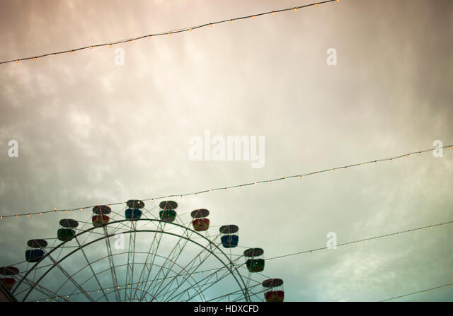 A ferris wheel and wires in a cloudy sky - Stock Image