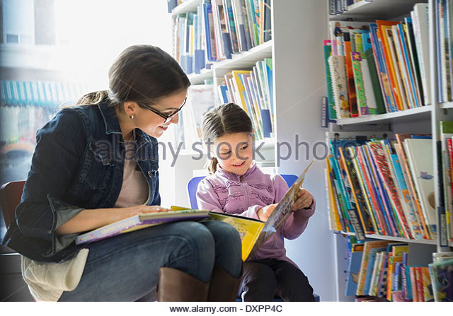 Mother and daughter reading book in bookstore - Stock Image