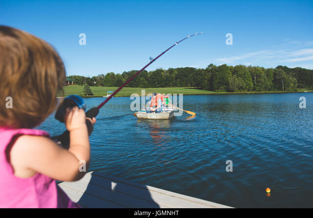 A child fishing on a dock at a pond in a rural area. - Stock Image