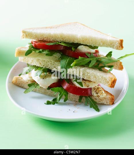 Toast with Tomato, Mozzarella, Mayonnaise and rocket salad on plate - Stock-Bilder