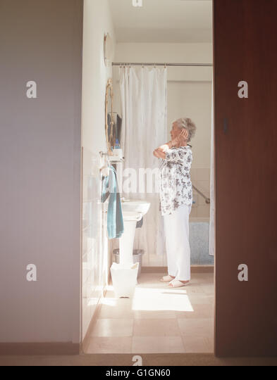 Full length indoor shot of elderly woman getting ready at dresser. Senior female getting ready in bathroom. - Stock Image
