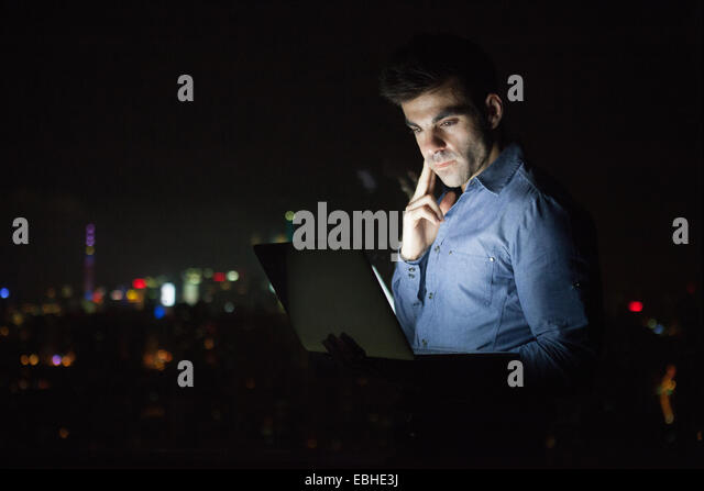 Young businessman looking at laptop in front of skyscraper office window at night, Shanghai, China - Stock-Bilder