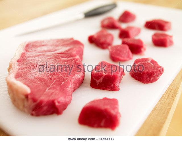 Cubed raw steak on cutting board - Stock-Bilder