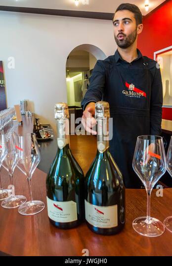 Reims, France, Bar man Serving Tourists Visiting Mumm Champagne Bar - Stock Image
