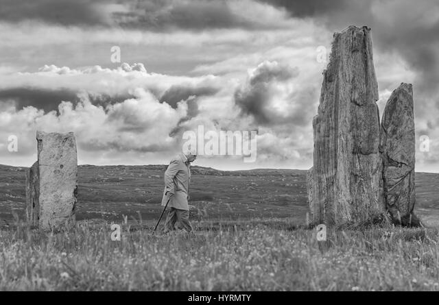 Old man walking around old stones - Stock Image