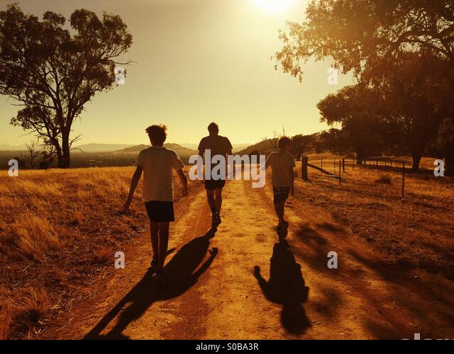 A father and his two sons waking into the sunset in Country Australia - Stock-Bilder