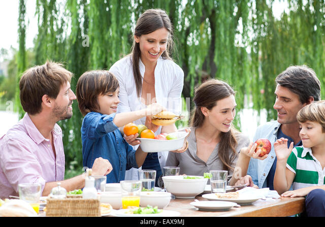 Family eating healthy meal together outdoors - Stock Image