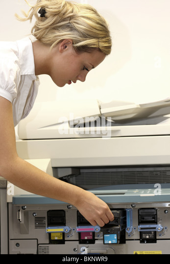 Young Business Woman Changing Printer Cartridge. Model Released - Stock-Bilder