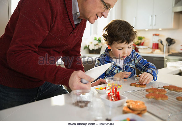 Grandfather and grandson decorating Christmas cookies together - Stock Image
