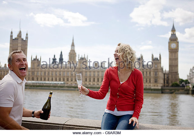 A middle-aged couple in front of the Houses of Parliament, opening a bottle of champagne - Stock Image