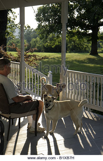 Arkansas Ozark Mountains Mountain View Country Oaks Bed and Breakfast man two dogs pet animal porch rest garden - Stock Image