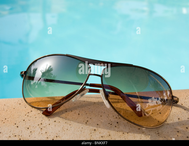Sunglasses at the poolside with reflections in the lenses - Stock Image