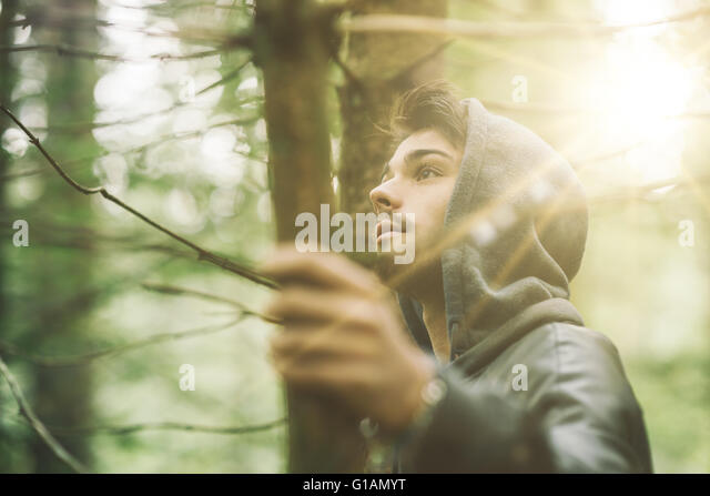 Hooded guy in the woods exploring nature, individuality and freedom concept - Stock Image