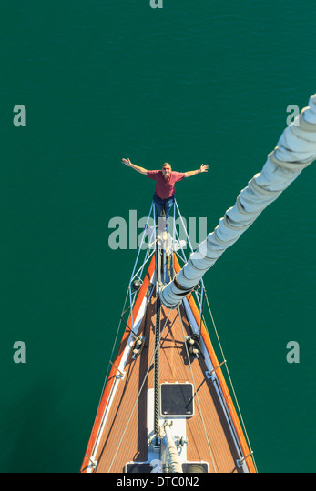 Senior man seen sailing from above with arms outstretched, San Diego, California, USA - Stock Image